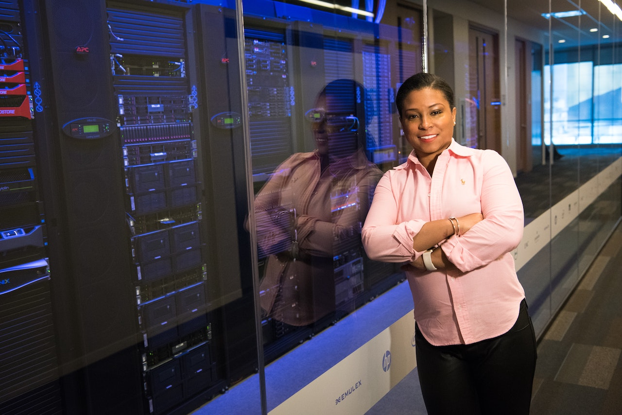 woman who is a managed service provider stands next to computer equipment